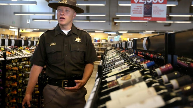 In this Thursday, July 2, 2015 photo, Utah Highway Patrol Sgt. Todd Royce talks about underage drinking at the Utah State Liquor Store in Holladay. Liquor bottles will bear sale tags in Utah this summer that remind adults that giving alcohol to minors can mean a possible $2,500 fine and up to a year in jail.