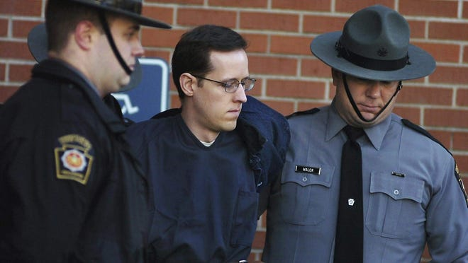 FILE- Eric Frein is led away by Pennsylvania State Police Troopers at the Pike County Courthouse after his preliminary hearing in Milford. Frein's parents are suing the state police and district attorney to obtain their firearms.