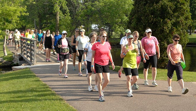 A long line of walkers doing the full marathon cross a small bridge in Pfiffner Pioneer Park during the 2014 Walk Wisconsin.