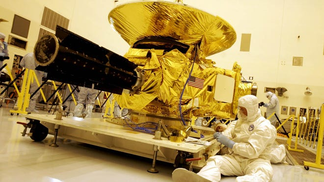 Technicians work on the payload for the New Horizons mission to Pluto on Nov. 4, 2005, at the Kennedy Space Center in Cape Canaveral, Fla.