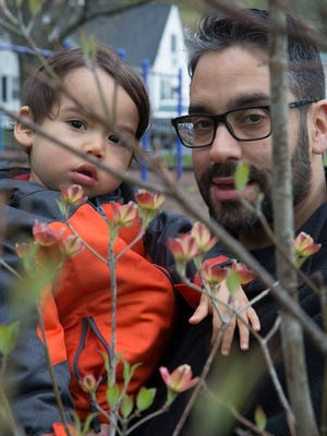Michael Pagan planted a tree for his son Kai, who is almost 2, as part of the Trees of Love program in Teaneck that lets residents plant trees to celebrate a birth, or wedding, or memorialize a loved one. They are shown here looking through the tree which has just begun to bud.