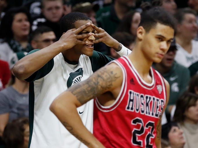 Michigan State forward Marcus Bingham Jr., standing next to Northern Illinois guard Rod Henry-Hayes (22), reacts after a teammate's three-point basket during the first half of an NCAA college basketball game, Saturday, Dec. 29, 2018, in East Lansing, Mich. (AP Photo/Carlos Osorio)