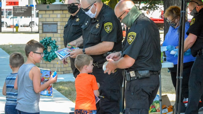 Members of the Schuyler County Sheriff's Office hand out coloring books to kids Tuesday on the lawn of the Schuyler County Courthouse.