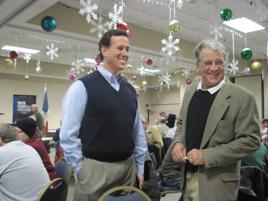 A smiling Rick Santorum wore a sweater vest  as he campaign in Davenport just prior to the 2012 Iowa caucuses. He was standing next to John Searles of Davenport.