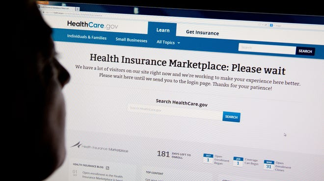 """A woman looks at the HealthCare.gov insurance exchange site showing a """"Please wait"""" page on Oct. 1, 2013."""