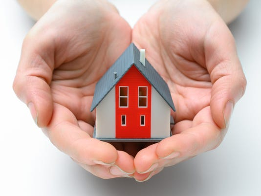 Red and gray model house in cupped hands on white background