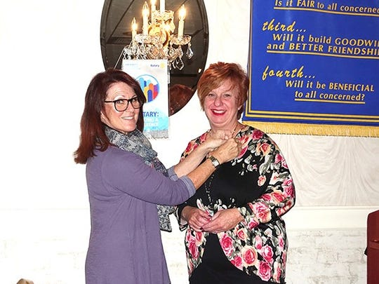 Alice Woods (right) receives her Rotary Club member