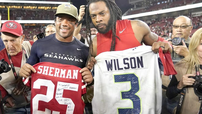 Seattle Seahawks quarterback Russell Wilson (left) exchanges jerseys with San Francisco 49ers cornerback Richard Sherman after a Nov. 11, 2019, game in Santa Clara, California. NFL teams will be prohibited from postgame interactions within six feet of each other, so players won't be allowed to exchange jerseys after games as part of the guidelines to help limit the spread of the coronavirus.The restrictions are outlined in the game-day protocols finalized Wednesday by the league and NFL Players Association.