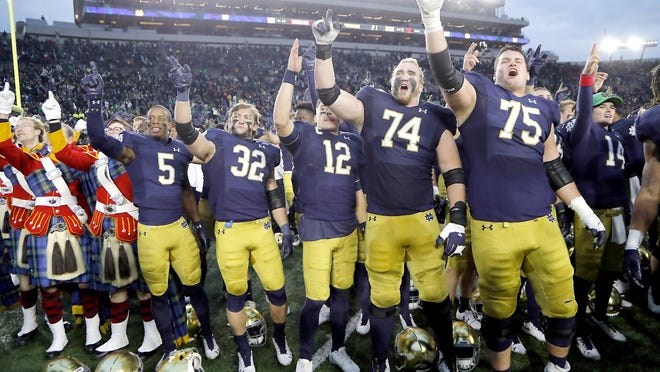 In this Nov. 2, 2019, file photo, members of the Notre Dame football team sing after a game against Virginia Tech in South Bend, Indiana. The Atlantic Coast Conference and Notre Dame are considering whether the Fighting Irish will give up their treasured football independence for the 2020 season play as a member of the league.