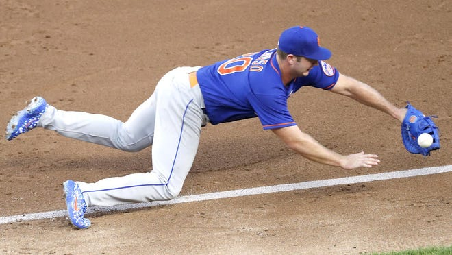 New York Mets first baseman Pete Alonso cannot reach the throw to first on an error by second baseman Robinson Cano which allowed Gleyber Torres of the New York Yankees to reach base in the third inning of Sunday's exhibition game at Yankee Stadium in New York.