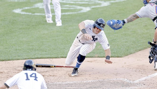Mike Tauchman scores the winning run for the New York Yankees under a tag attempt by New York Mets catcher Wilson Ramos during the eighth inning of the first game of Sunday's doubleheader at Yankee Stadium.