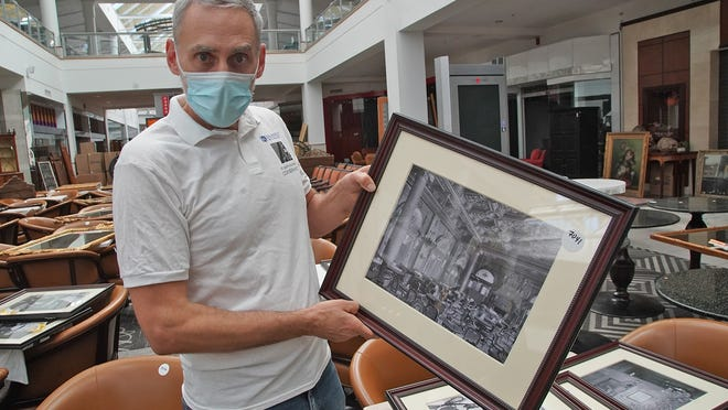 More than 15,000 items from the famed Waldorf Astoria hotel in New York City are being auctioned off at the former Silver City Galleria mall in Taunton.   Art consultant to the sale Cliff Schorer holds a picture of the Waldorf Astoria on Wednesday, Oct. 14, 2020.  Taunton Gazette | Mike Gay