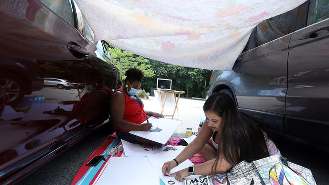 Maria Curtis, right, and Danielle Mayers, left, both of Norwell work on their signs underneath the cover of a blanket in the parking lot of the Cushing Center on Thursday, July 2, 2020.
