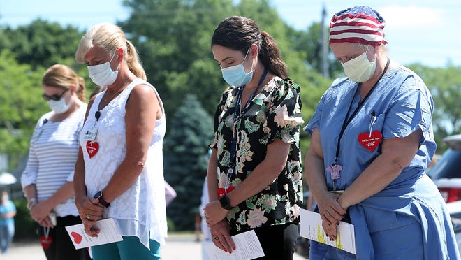 Staff members at South Shore Hospital bow their heads during a moment of silence for the 140 patients who have died as a result of COVID-19 at the hospital during a memorial service on Thursday, July 2, 2020.