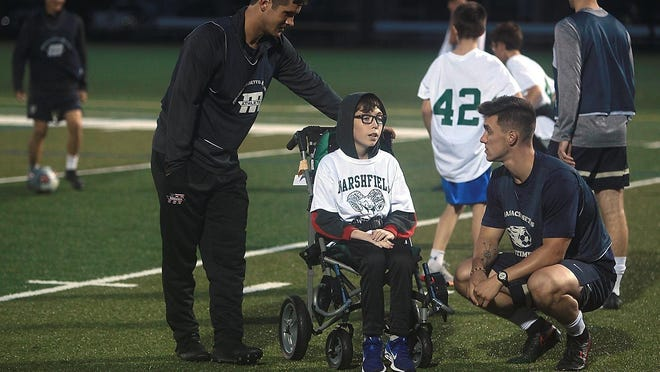 Thomas Schmid, 13, of Marshfield chats with senior Jake Pfor of Weymouth while senior Adam Crawford of Kingston helps him during United soccer game between Marshfield and Mass. Maritime last year.