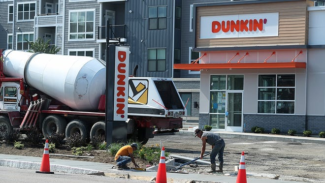 Workers lay down a new sidewalk while working in front of the new Dunkin' in the Hingham Shipyard on Rt. 3A on Thursday, July 2, 2020.