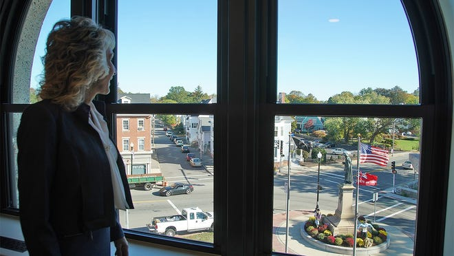Taunton Mayor Shaunna O'Connell looks out at the Robert Treat Paine statue and downtown Taunton from the meeting room near her office in the rebuilt Taunton City Hall, Oct. 8, 2020.