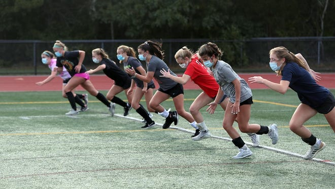 Members of the field hockey team sprint off the line during a conditioning exercise at practice Friday.