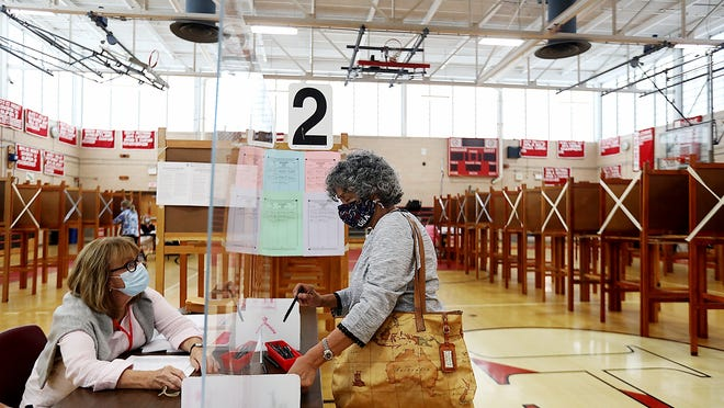 Concepcion Rayna of precinct 2 picks up her pen and ballot from Kate Boland while voting on primary day at the high school on Tuesday, Sept. 1, 2020.