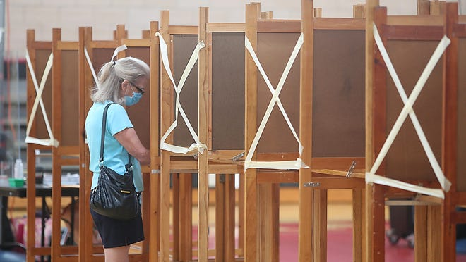 Karen Benjamin of precinct 1 fills in her ballot next to booths that were closed to maintain proper social distancing inside the gym at the high school on Saturday, June 27, 2020.