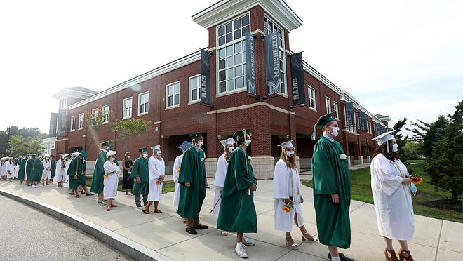 Marshfield High seniors wait on the sidewalk before filing onto the football field for their graduation ceremony on Friday, July 24, 2020.