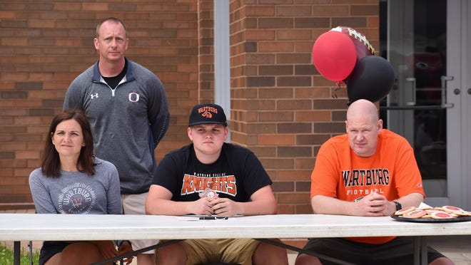 "From left to right are Taryn Dunlap, Ben Dunlap and Mike Dunlap, and standing behind them is Orion football coach Chip Filler. Ben Dunlap signed to play football at Wartburg College. ""There's never been a better leader in our program,"" Filler said, who noted Dunlap was a three-year starter, an All-Conference selection and a straight-A student."
