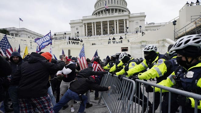 Trump supporters try to break through a police barrier, Wednesday, Jan. 6, 2021, at the Capitol in Washington. As Congress prepares to affirm President-elect Joe Biden's victory, thousands of people have gathered to show their support for President Donald Trump and his claims of election fraud. AP Photo/Julio Cortez