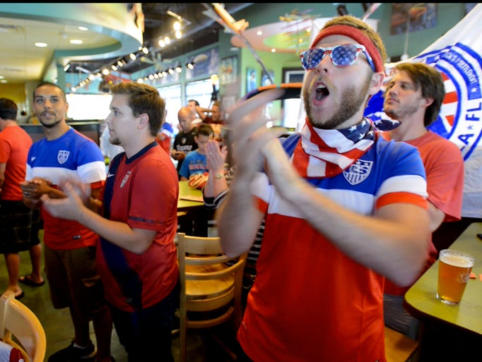 Soccer fans including Kevin Mooney, right, gather at Mellow Mushroom to cheer on team USA as they take on Ghana in the World Cup.