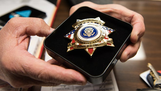Wicomico County Sheriff Mike Lewis holds a badge created for the Inauguration of Donald Trump.  All 25 Wicomico County deputies in attendance will receive a badge like this one.