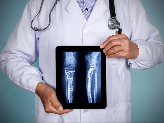 doctor showing xray on digital tablet