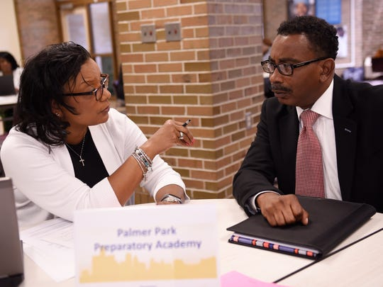 Dr. Georgia Hubbard, left, principal at Palmer Park Prep Academy, interviews and then hires Robert Davis for a teacher position during a job fair at Benjamin Carson School for Science and Medicine.