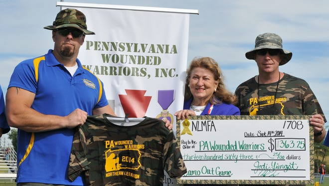 The Pennsylvania Wounded Warriors group provides help to veterans. In this file photo, founder of Pennsylvania Wounded Warriors Helen Sajer, wife of the late Maj. Gen. Gerald Sajer, accepts a check from Northern Lebanon Midget Football Association Coaches Tom Borky (left) and Brian Bakos.