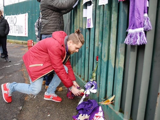 Supporters lay flowers and scarves to pay their homage to Davide Astori, outside the Artemio Franchi stadium, in Florence, Italy, Sunday, March 4, 2018. Fiorentina captain Davide Astori was found dead in his hotel room on Sunday at the age of 31 after a suspected cardiac arrest before an Italian league match. The defender, who has also played 14 times for Italy's national team, was discovered by Fiorentina staff when he failed to show up for breakfast at the hotel in Udine. Fiorentina's game at Udinese in northeast Italy was called off, along with all fixtures in the country's top two divisions. (Maurizio Degl'Innocenti/ANSA via AP)