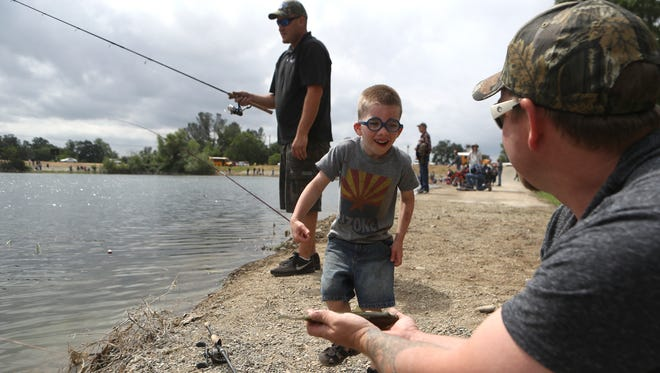 Meadow Lane elementary school student Kyle Maddox, 5, checks out the fish he just caught Thursday during the J.F. Shea 41st annual Fishing Party at the Shea Sand and Gravel Pond in Redding.