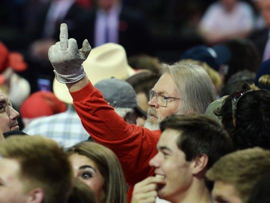 A man flips off the media at a Donald Trump rally at