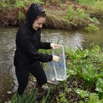 Town of Poughkeepsie resident Christina Joerg removes litter from the Casperkill Creek on the campus of Vassar College during the annual Riverkeeper Sweep.