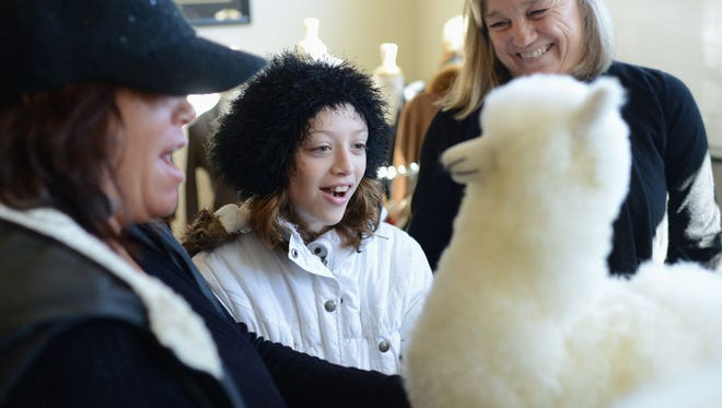 Ten-year-old Mercedes Marino Lambert reacts to an alpaca stuffed animal along with her grandmother Kim Melcore, left, and Sabamba owner Sally Schmidt, right, during an open house Saturday at Sabamba Alpaca Ranch and Bed & Breakfast in Lawrence.