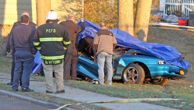 Emergency personnel work at the scene of a fatal car crash on College Ave. in Port Chester Nov. 21, 2014. One person was reported to be dead and another taken from the scene by ambulance.  The crash occurred two blocks from Port Chester High School.