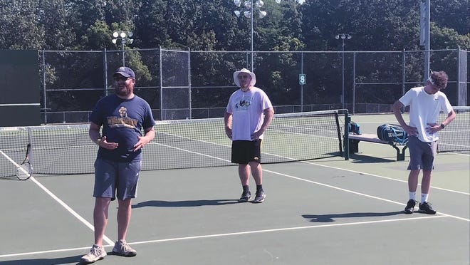 While practicing social distancing, William Chrisman tennis coach Jason Grubb, left, visits with his team Monday morning at Santa Fe Trail Park in Independence.