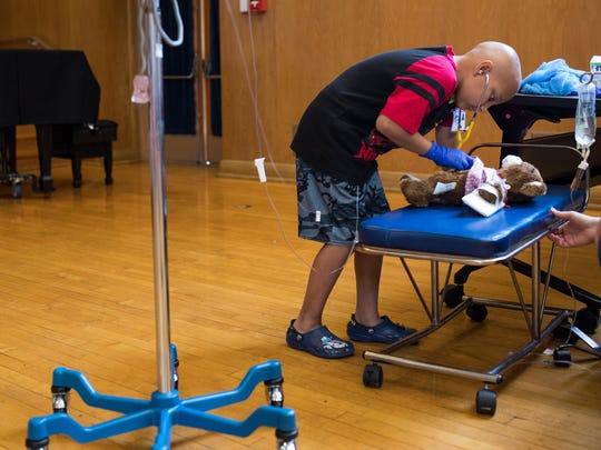 Eight-year-old Austin Sanchez checks the hart beat of his teddy bar during a Teddy Bear Hospital event at Driscoll Children's Hospital auditorium on Wednesday, Aug. 16, 2017.