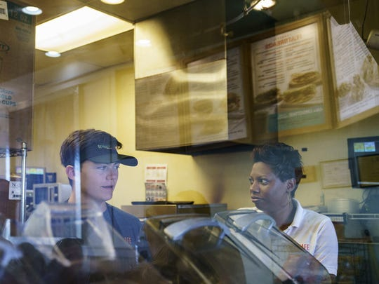 Nicole Drake, co-owner of Tropical Smoothie Cafe franchises in Gainesville and Ashburn, Va., talks with employee Matthew Dumm, left, in the Ashburn, Va., store.