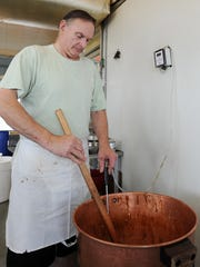 Tom Ibach owner of Dolle's on Rehoboth Avenue  makes caramel popcorn as businesses prepare for the holiday weekend in Rehoboth Beach.