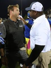 Towson head coach Rob Ambrose (left) greets Delaware head coach Dennis Dottin-Carter after Delaware's 20-6 win at Delaware Stadium Saturday.