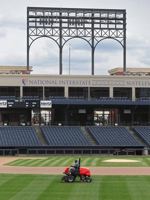A member of the grounds crew mows the outfield of Canal Park, Tuesday, April 14, 2020, in Akron, Ohio. The RubberDucks were scheduled to play the Binghamton Rumble Ponies in their home opener on Friday, April 17, but the season has been delayed due to the coronavirus pandemic.
