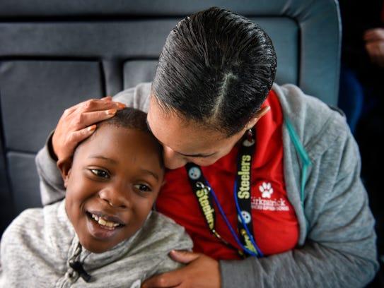 Justin Robinson gets a hug from fourth-grade teacher