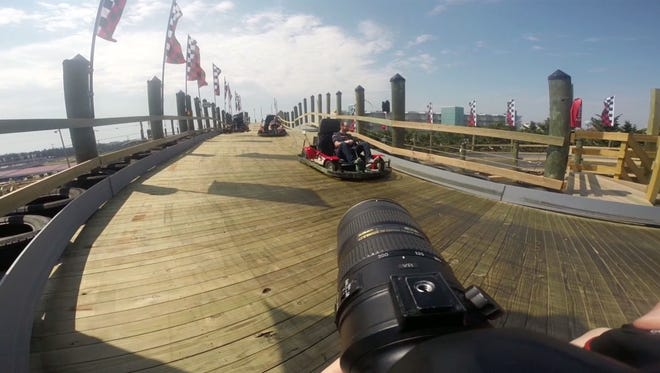 Photographer Joe Lamberti shoots reporter Jon Bleiweis and Jolly Roger's Dean Langrall as they cruise through Jolly Roger SpeedWorld's new Cyclone Cart Coaster on May 18, 2015, in Ocean City, Md.