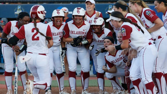 Oklahoma's Sydney Romero (2) is greeted at home plate by her teammates after hitting a home run against Auburn in the third inning of the first game of the best of the best of three  championship series during an NCAA college softball game in the NCAA Women's College World Series in Oklahoma City, Monday, June 6, 2016. (AP Photo/Sue Ogrocki)