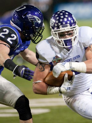 In this Dec. 20, 2013 file photo, Mount Union's Luke Meacham gains yards against Wisconsin-Whitewater's Andrew Keister (22) during the first half of the NCAA Division III championship college football game in Salem, Va.