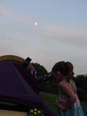 In this July 28, 2015, photo, Elizabeth Lizzy Myers, 5, gazes through a telescope at the Warren Rupp Observatory in Bellville, Ohio.