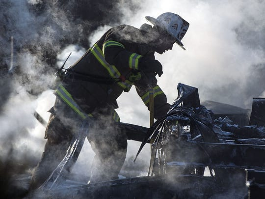 A firefighter picks up debris left from a workshop fire, which spawned from an out of control burn fired, according to the property owner on Monday, February 6, 2017. Thirteen fire companies from Adams County and Maryland respond.